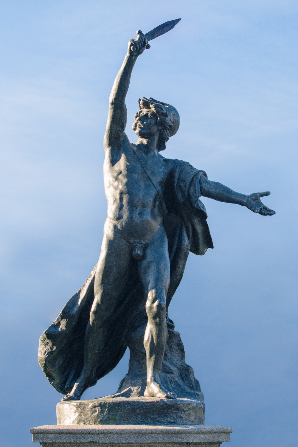 man with wings statue under blue sky during daytime