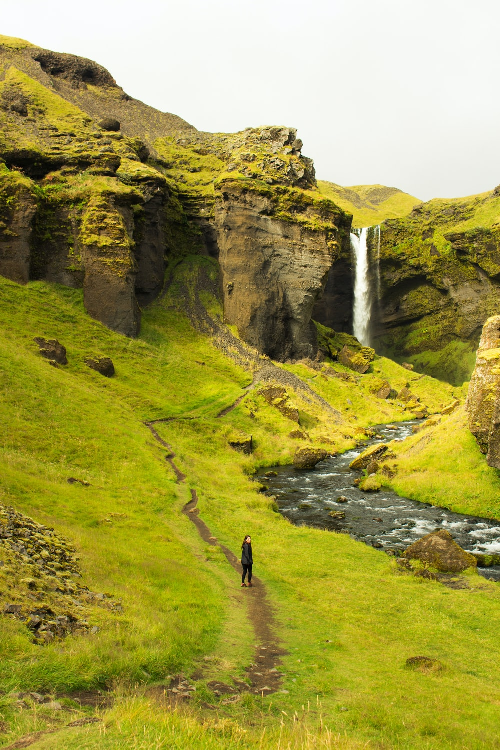 person walking on green grass field near waterfalls during daytime