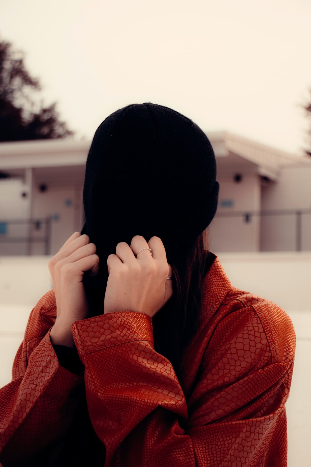 woman in red knit sweater covering face with black knit cap