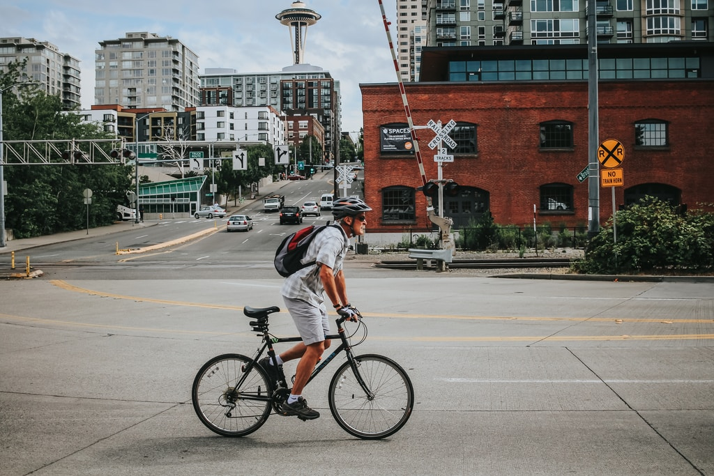 man in gray shirt riding on bicycle on road during daytime