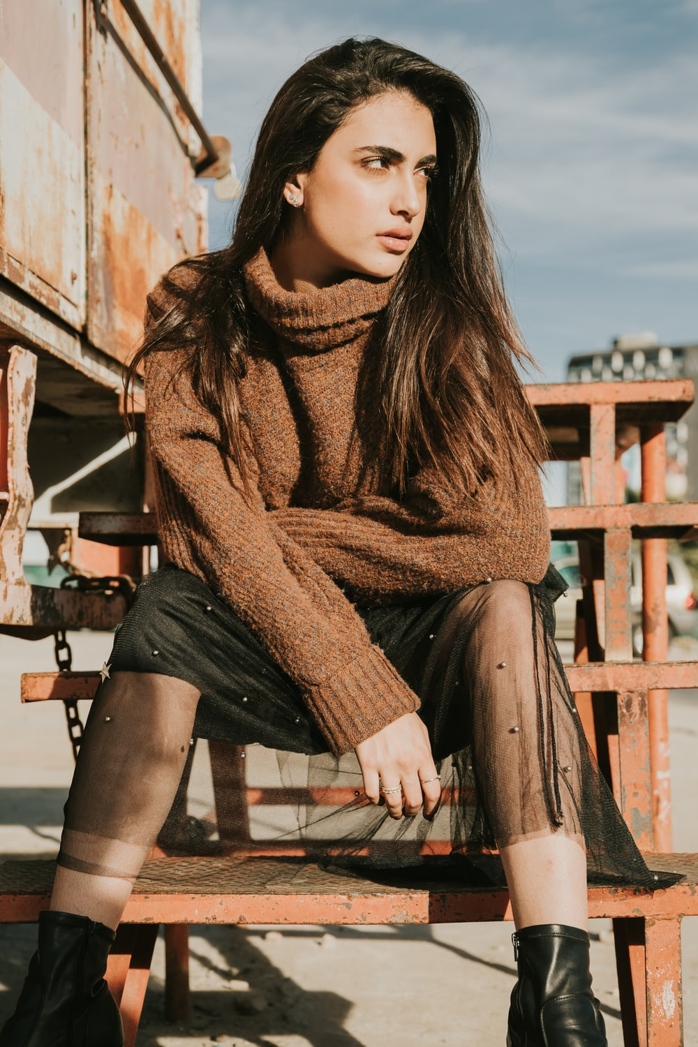 woman in brown sweater sitting on brown wooden bench during daytime