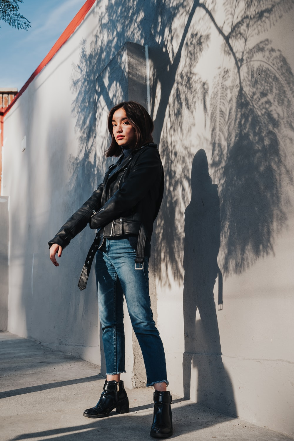 woman in black leather jacket and blue denim jeans standing beside white wall