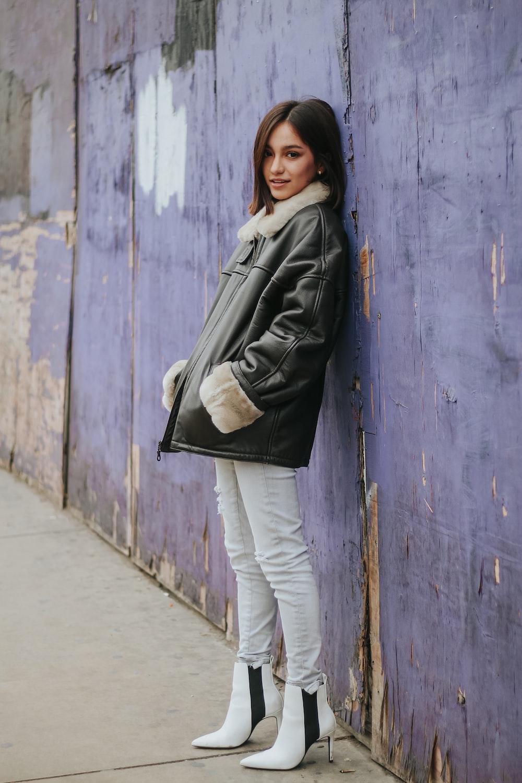 woman in gray jacket and white pants standing beside blue wooden door