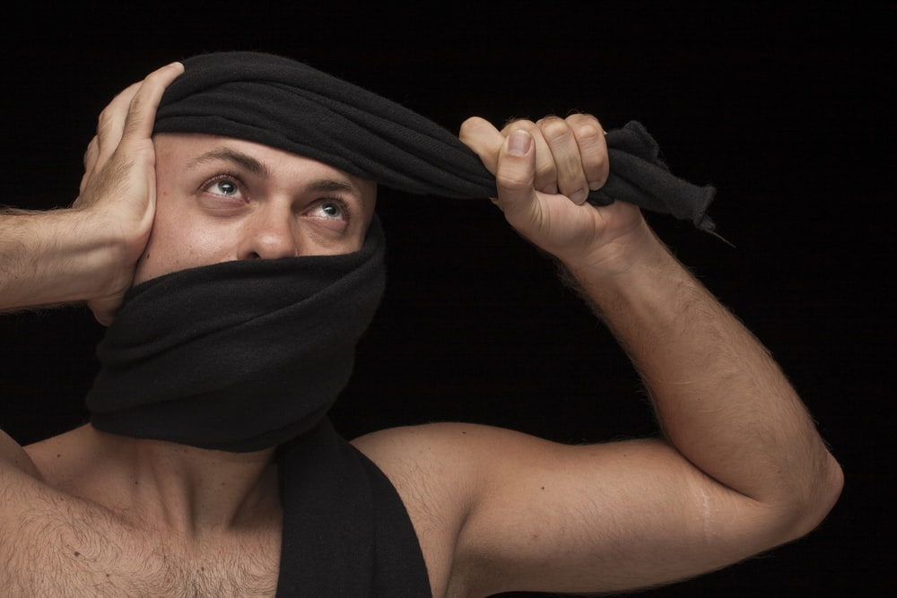 woman in black tank top covering her face with black scarf