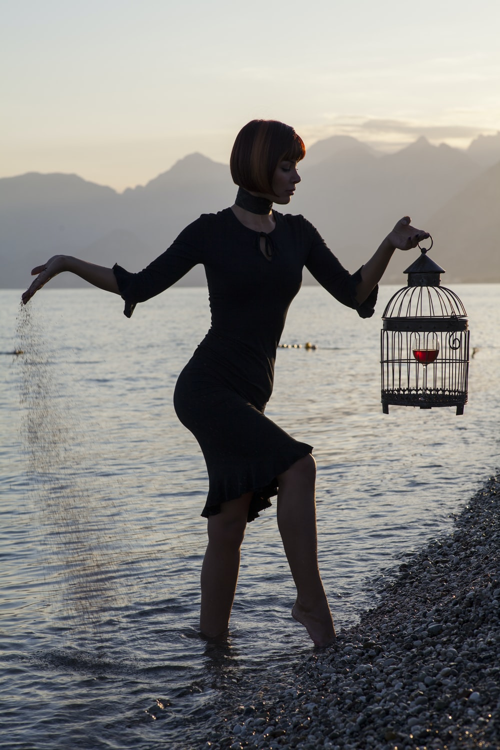 woman in black long sleeve dress holding white and black bird cage on water during daytime