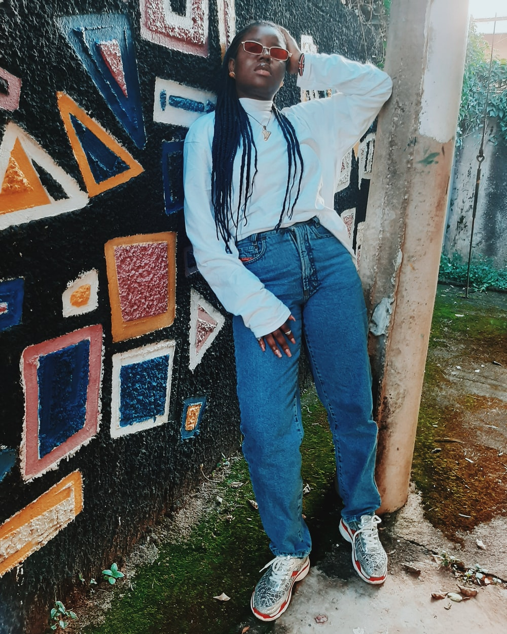 woman in blue denim jeans standing beside wall with graffiti