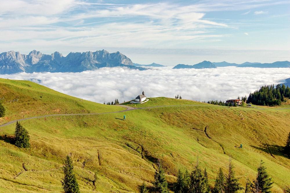 green grass field near mountains under white clouds during daytime