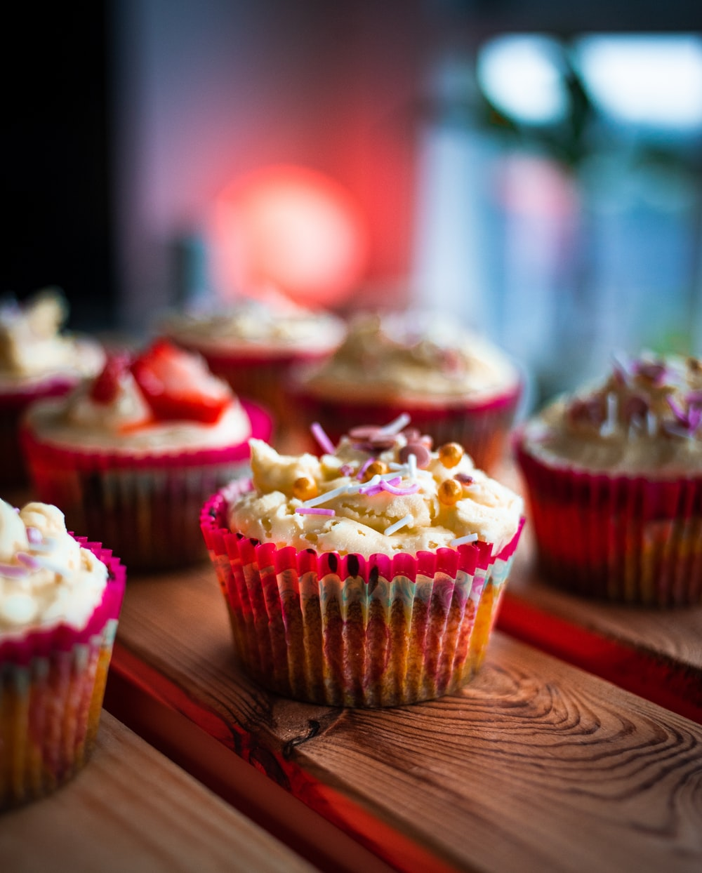 pink cupcake on brown wooden table