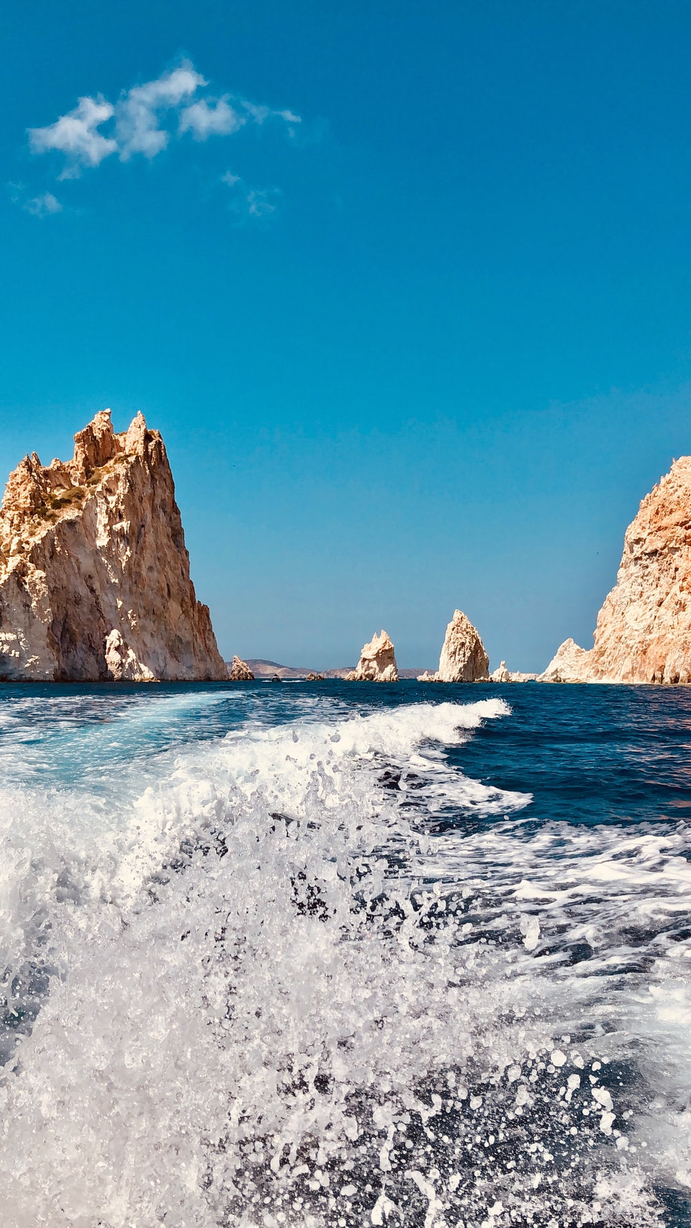 brown rock formation on sea under blue sky during daytime