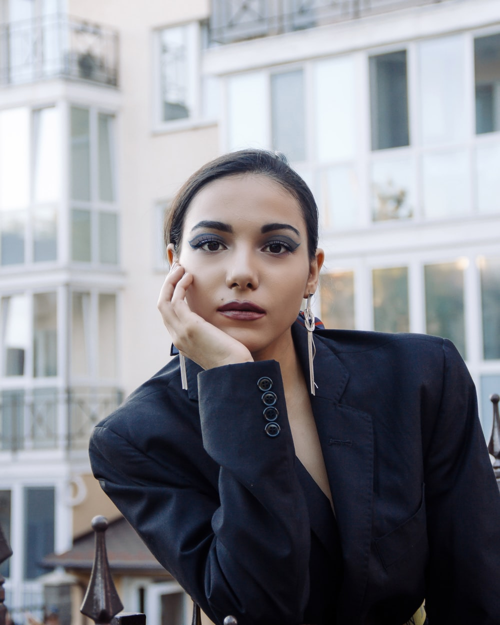 woman in black blazer holding her face