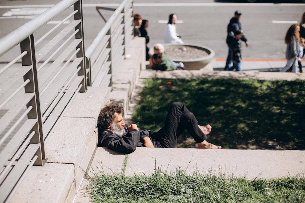 man in black long sleeve shirt lying on green grass field during daytime