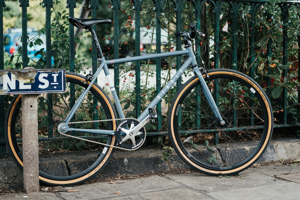 blue and black road bike beside white wooden fence