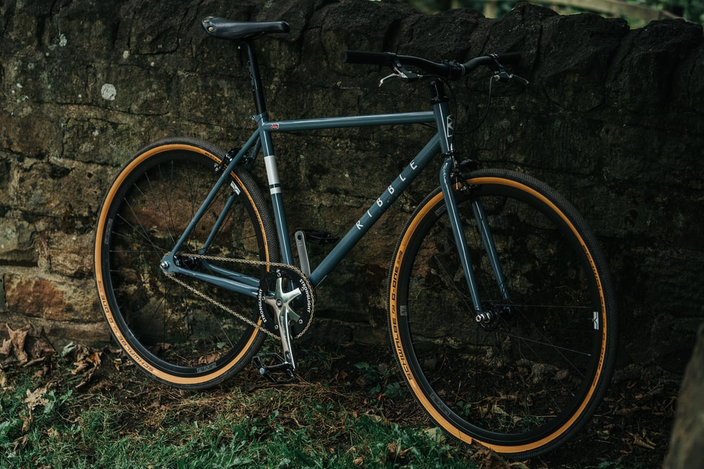 black and gray road bike leaning on wall