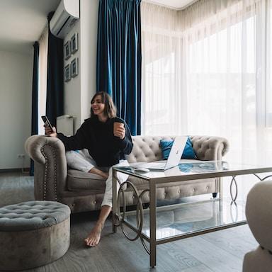 woman in black long sleeve shirt sitting on gray sofa chair