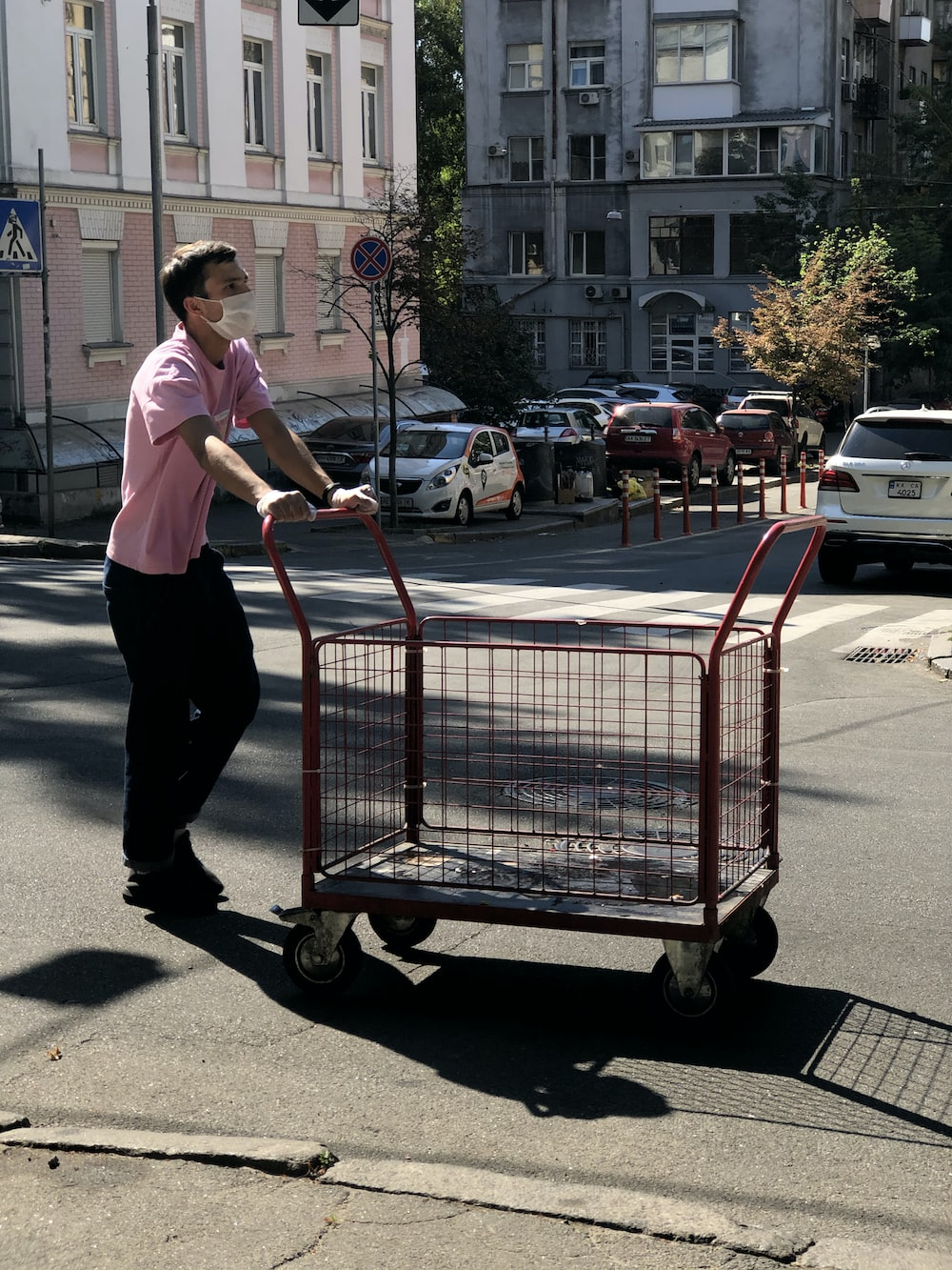 woman in white shirt and black pants holding red shopping cart