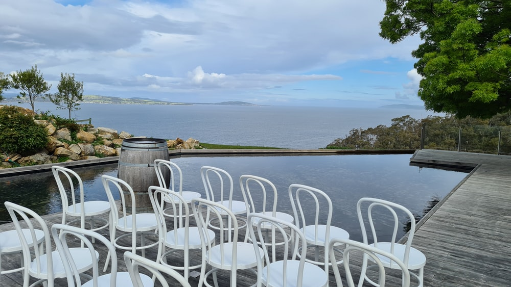 white plastic chairs near body of water during daytime