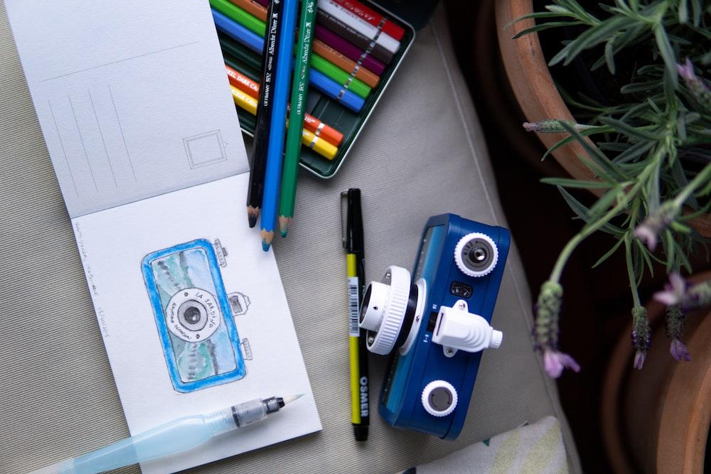 blue and white camera on white printer paper