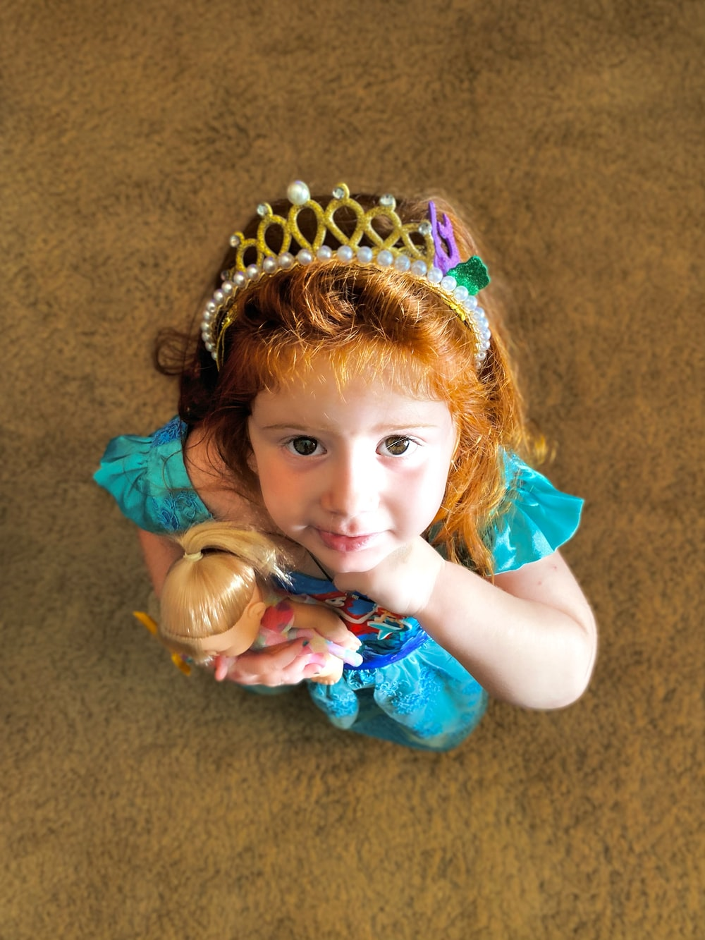 girl in teal sleeveless dress with gold crown