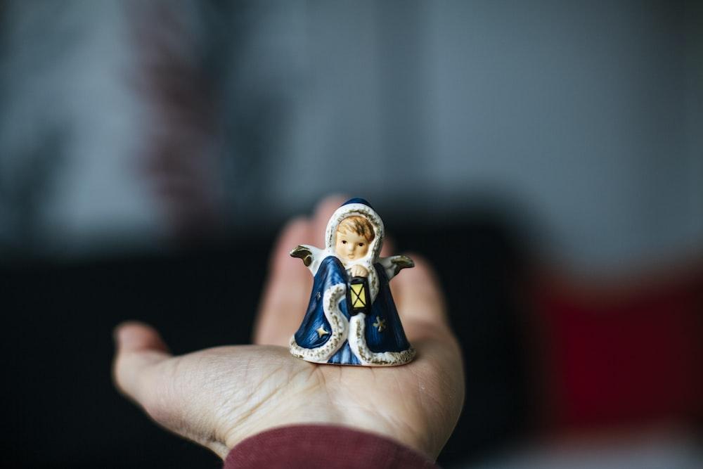 person holding white and blue ceramic figurine
