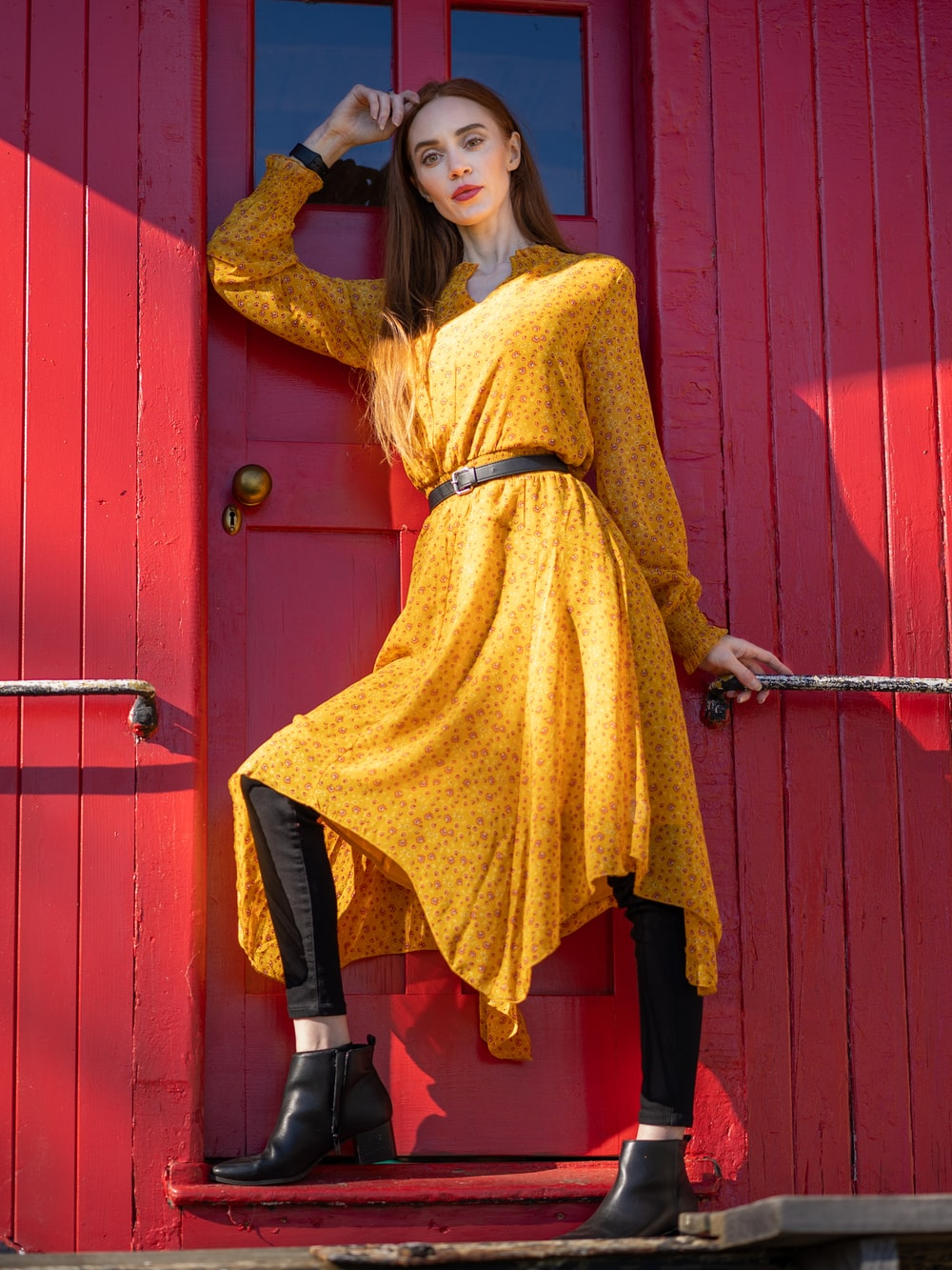woman in yellow long sleeve shirt and black pants leaning on red wooden door