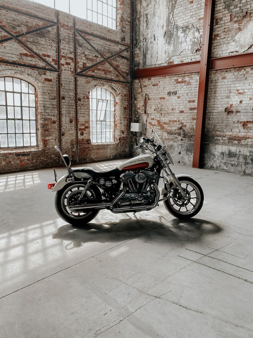 black cruiser motorcycle parked beside brown brick wall