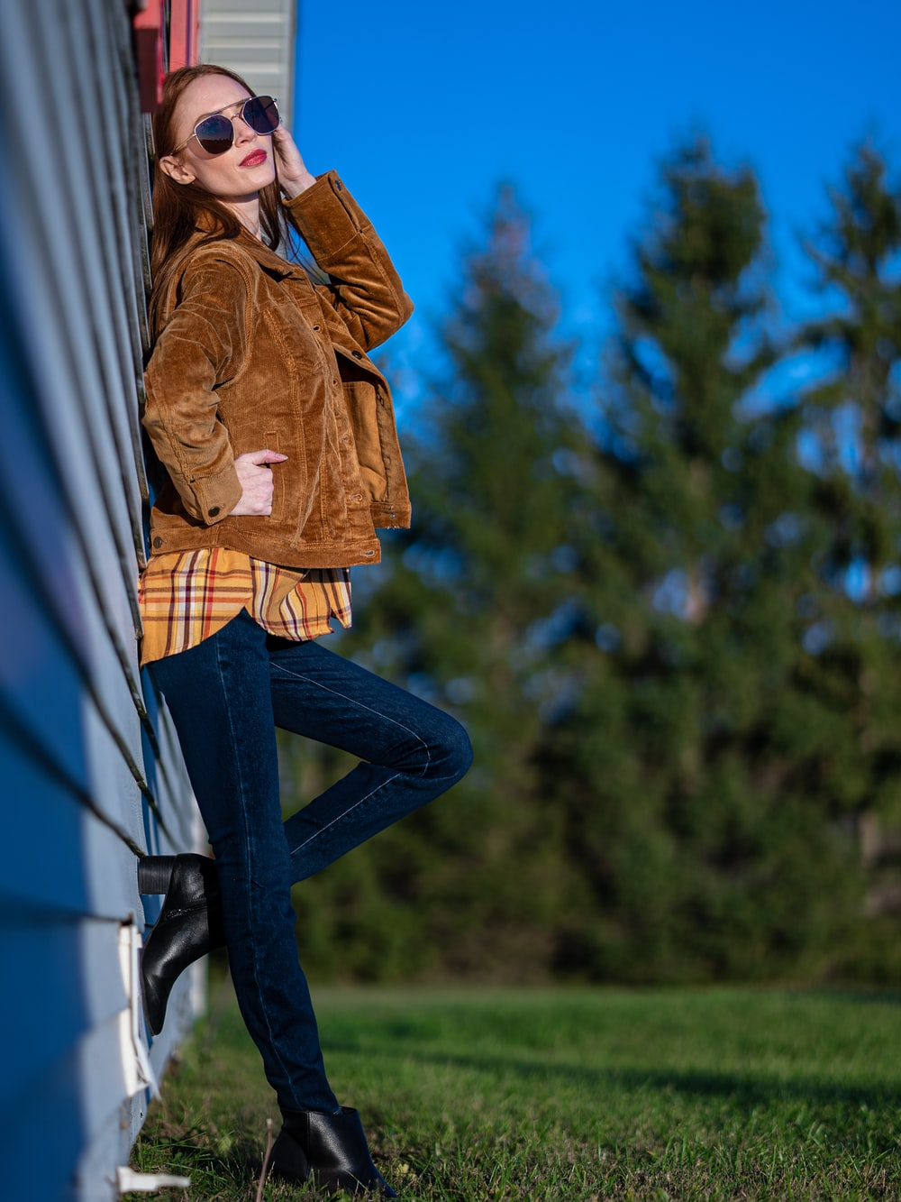 woman in brown jacket and blue denim jeans standing near white wall during daytime