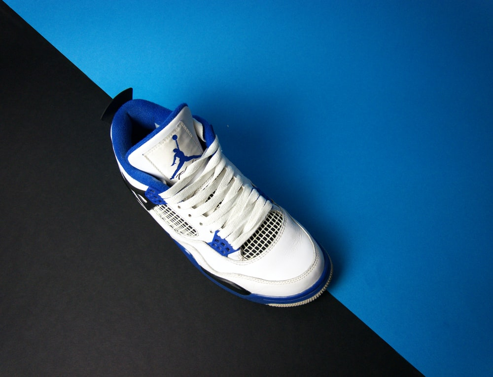 white and blue nike athletic shoe