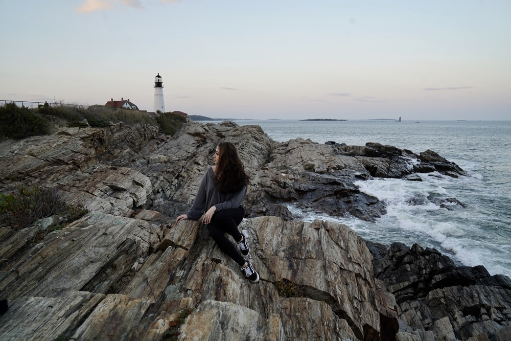 woman in black jacket sitting on rock formation near sea during daytime