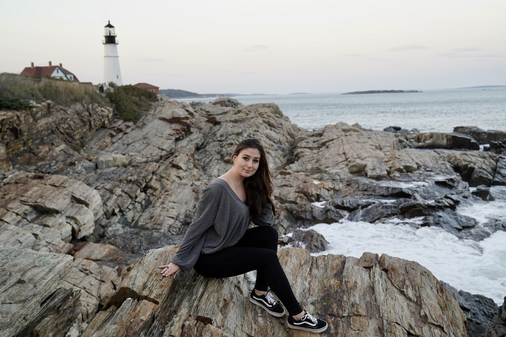 woman in gray sweater and black pants sitting on rock near body of water during daytime