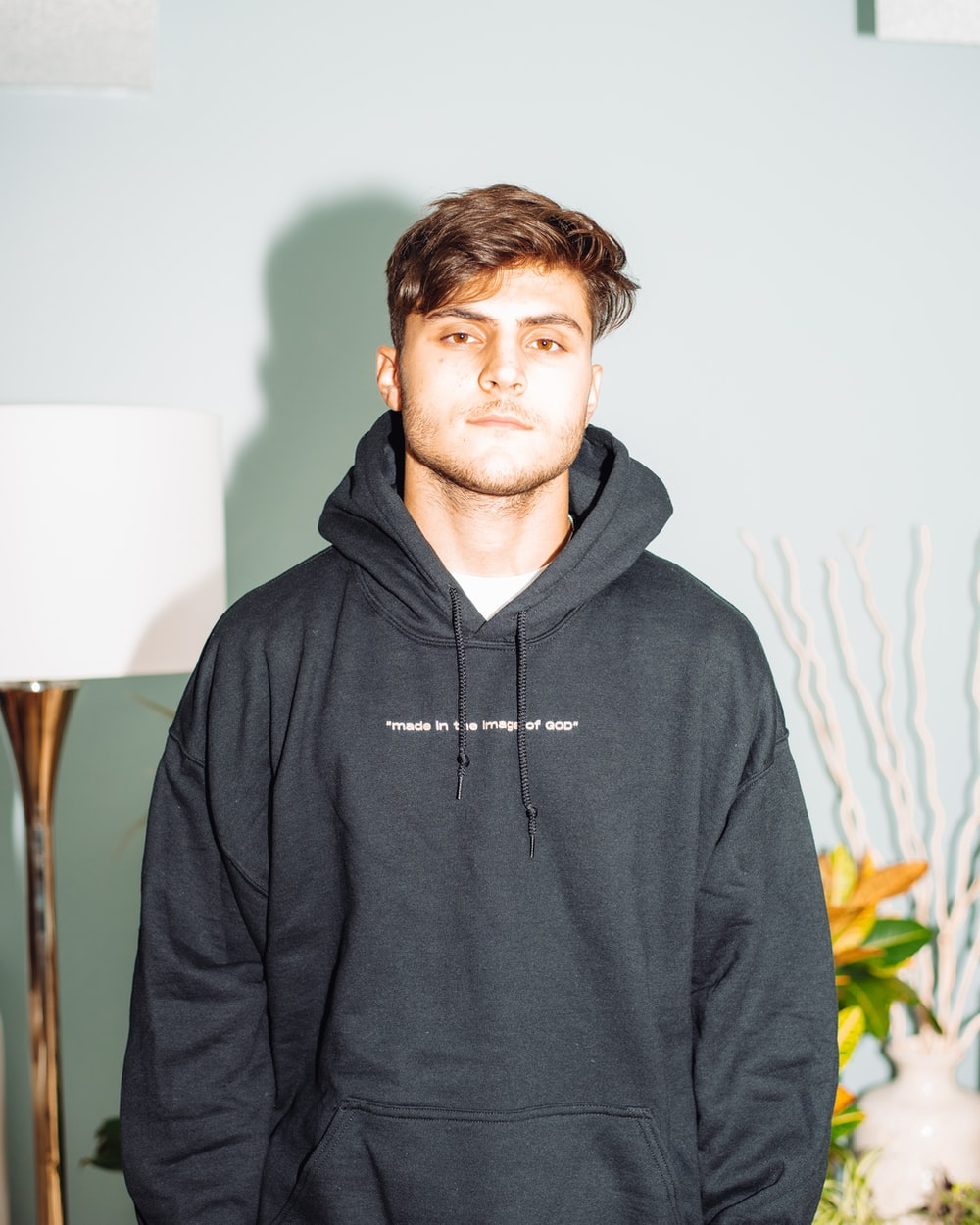 man in gray hoodie standing near white wall