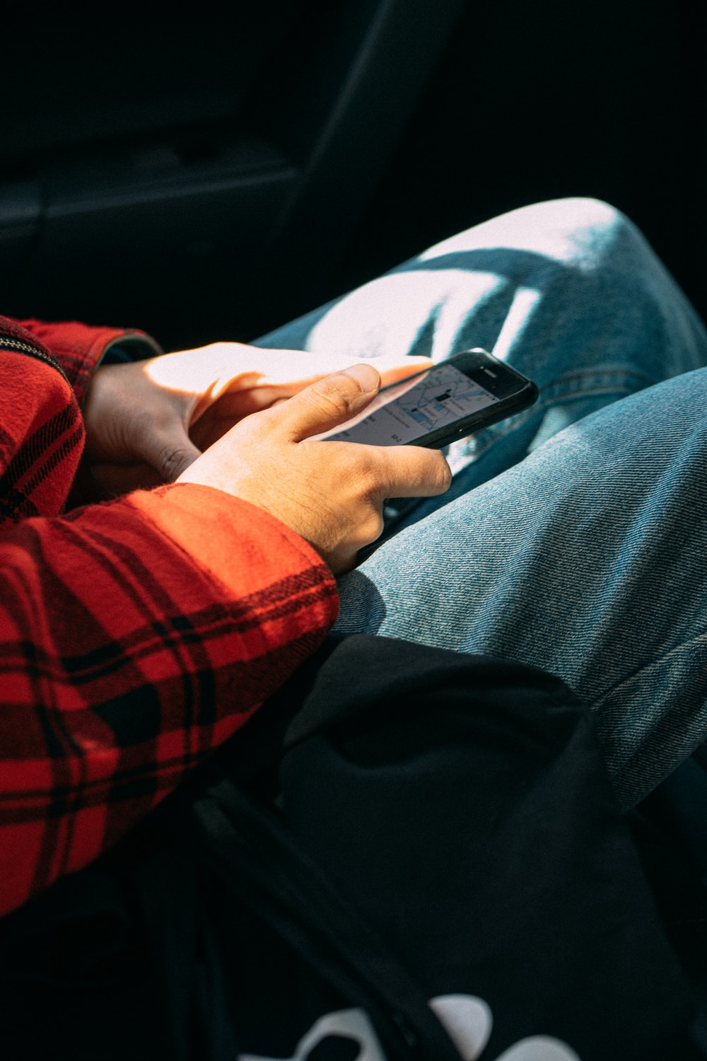 person in red and black plaid long sleeve shirt holding black smartphone