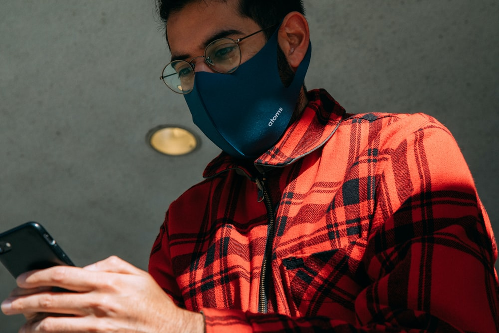 man in red and black plaid button up shirt wearing blue mask
