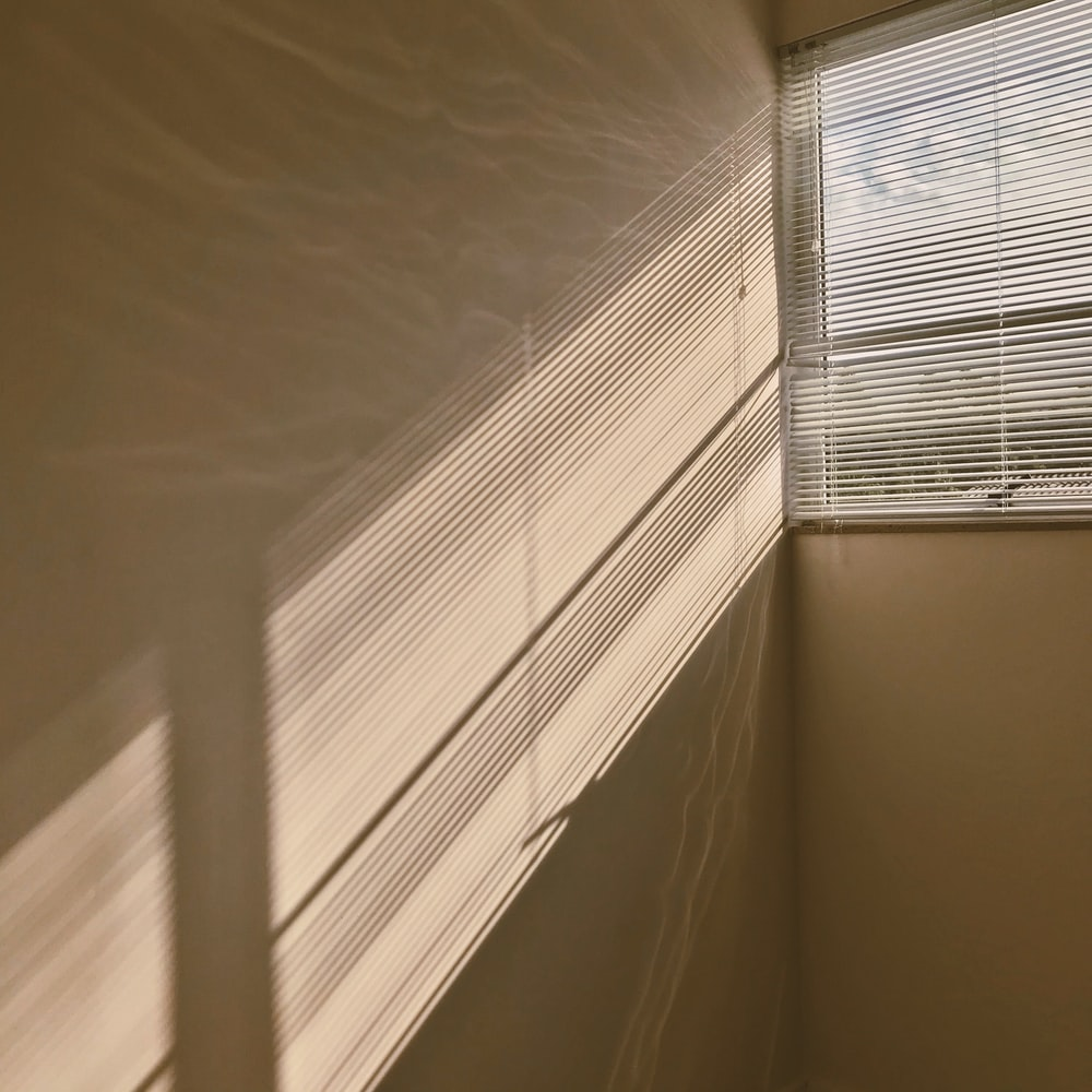 white window blinds on white wall