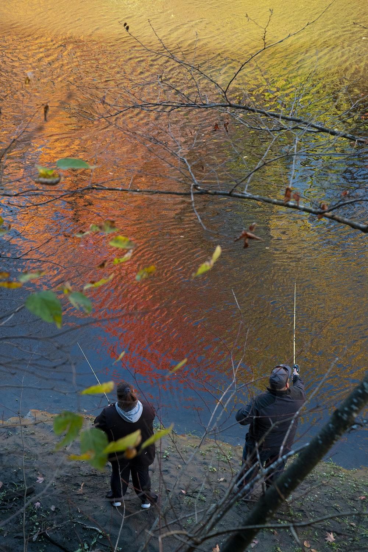 people fishing on river during daytime
