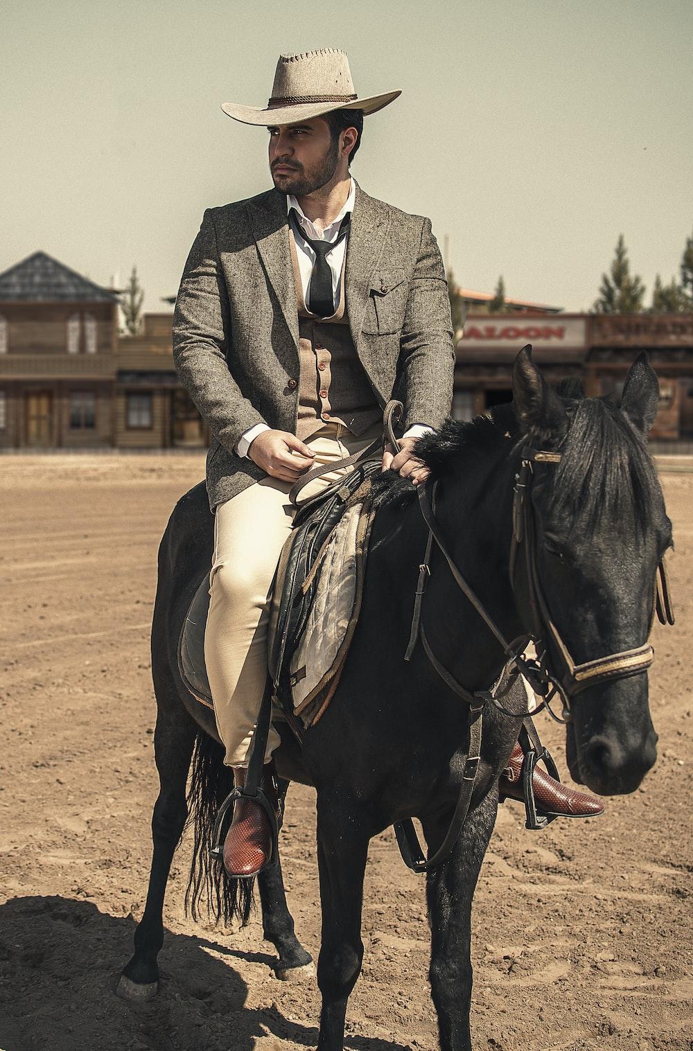man in gray coat riding black horse during daytime