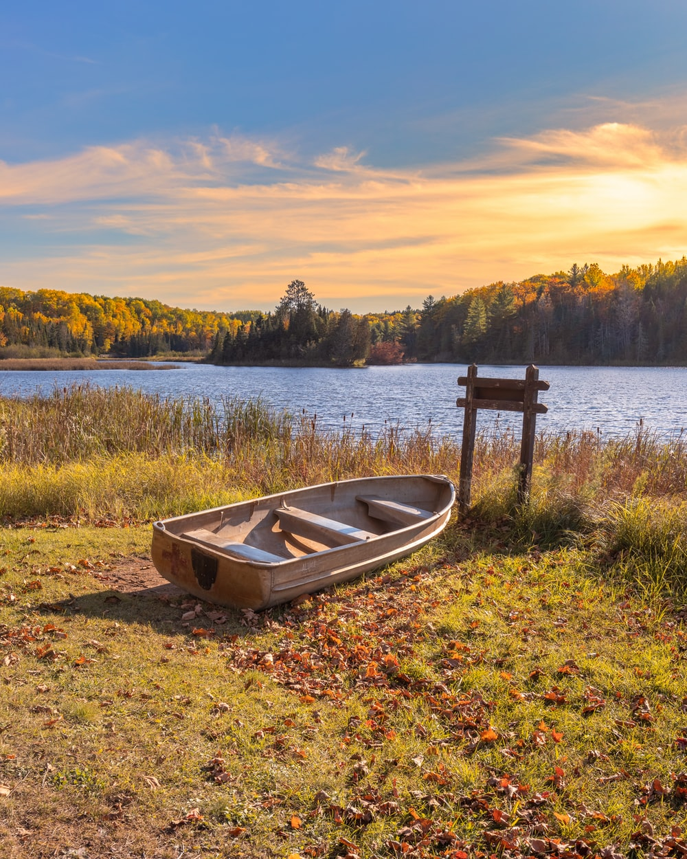 white and brown boat on green grass near lake during sunset