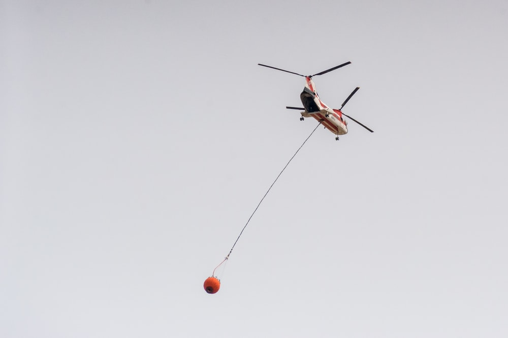 red and white helicopter flying in the sky