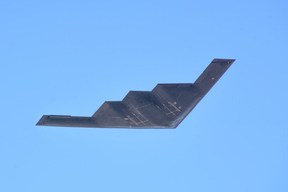 black plane under blue sky during daytime