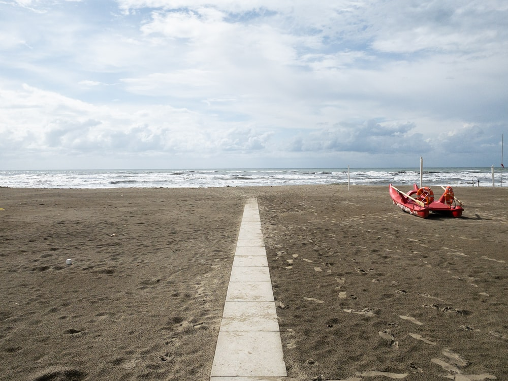 red boat on beach shore during daytime