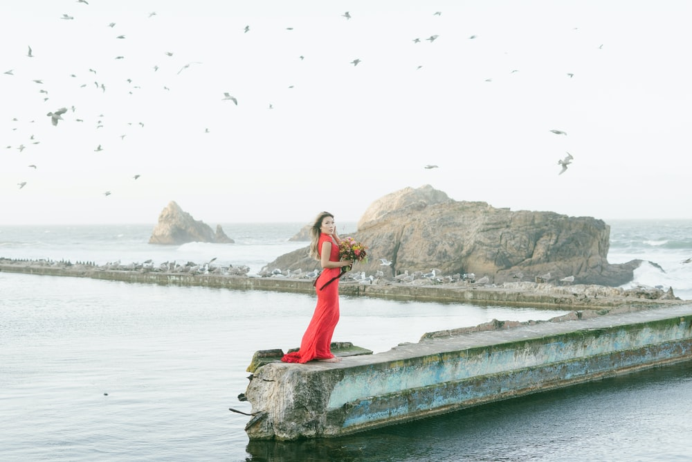 woman in red dress standing on gray concrete dock during daytime