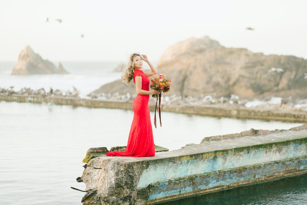 woman in red dress standing on concrete dock during daytime