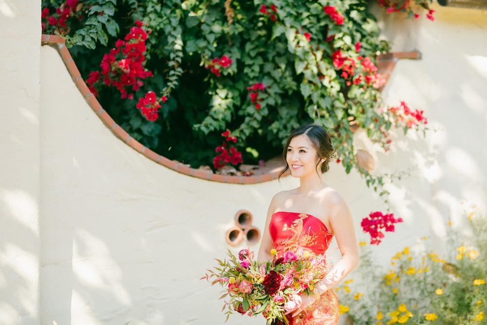 woman in pink and white floral tube dress holding bouquet of flowers