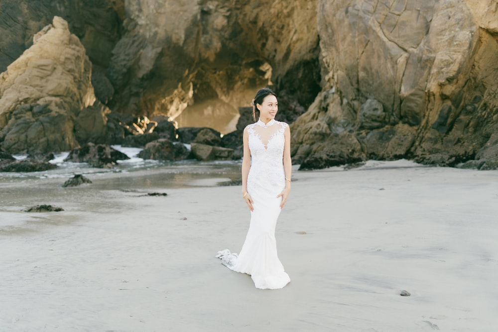 woman in white dress standing on white sand beach during daytime