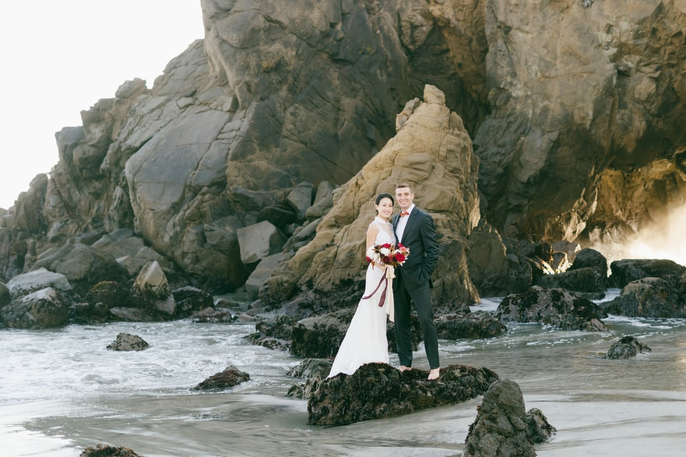 woman in white wedding gown standing on rock formation near body of water during daytime