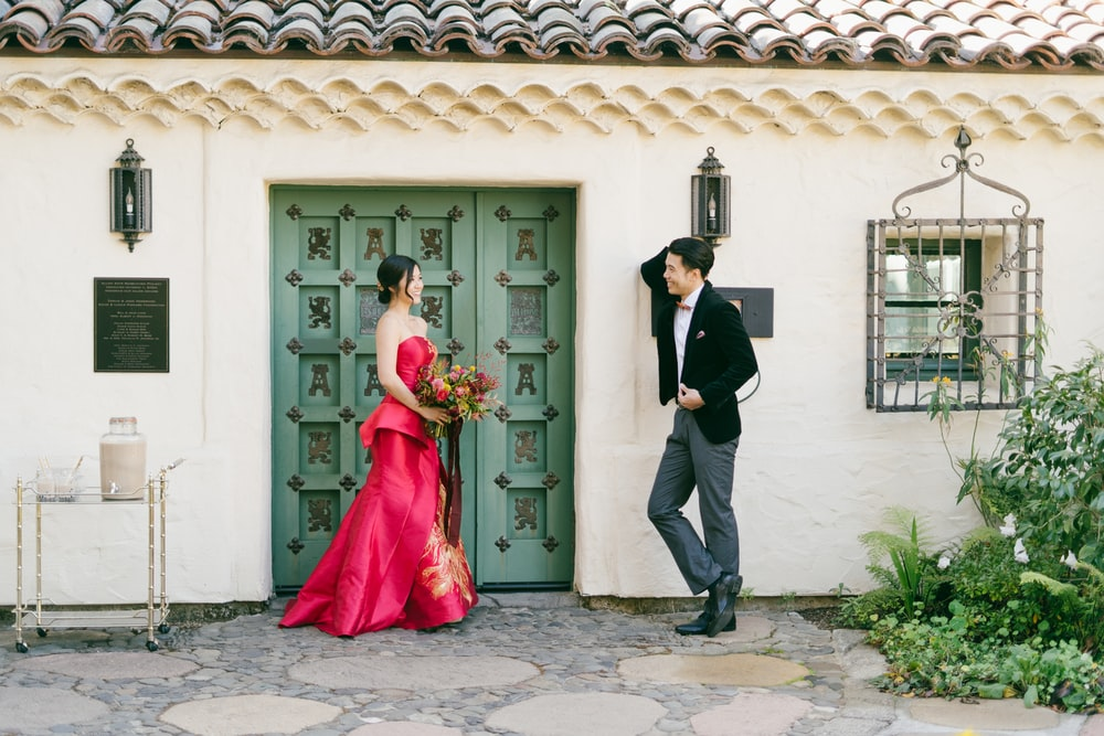 man in black suit jacket and woman in red dress standing near white wooden door during