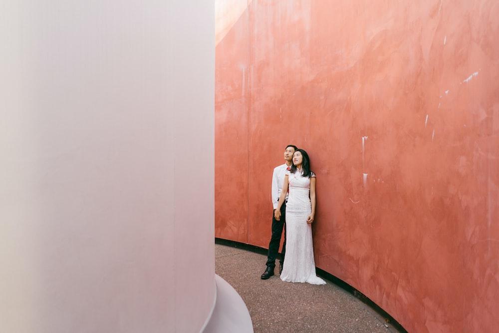 man and woman standing beside brown wooden door