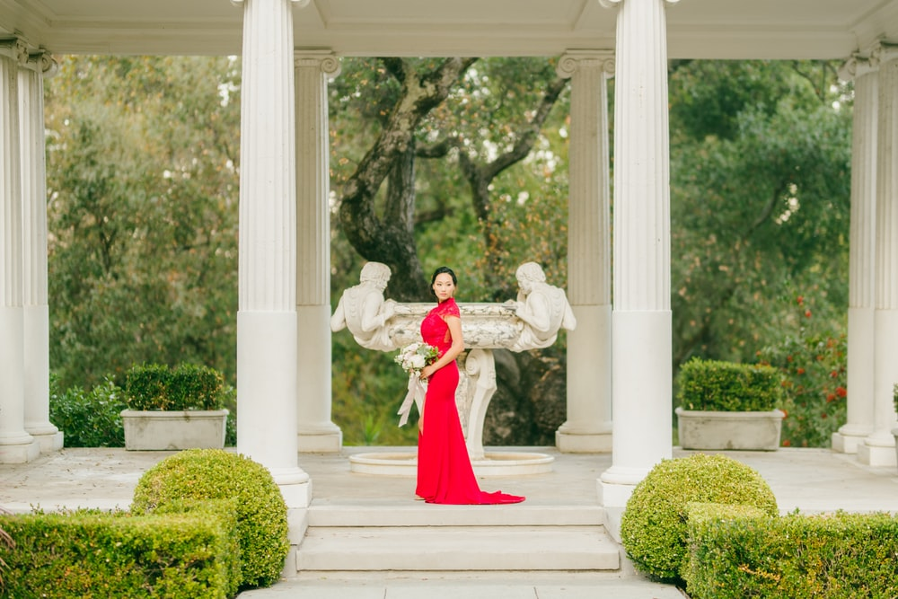 woman in red dress standing on white concrete staircase