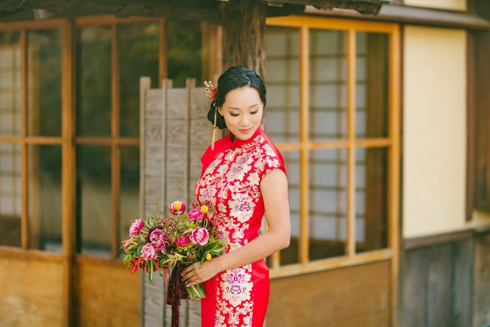 woman in red and white floral dress holding bouquet of flowers