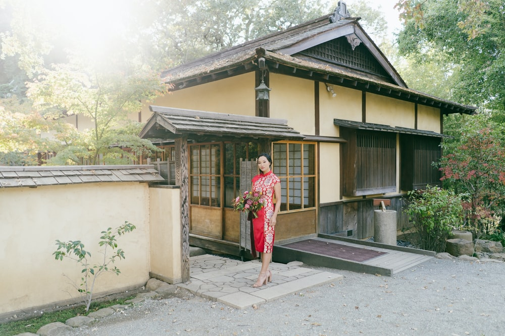 woman in red and white floral dress standing near brown wooden house during daytime