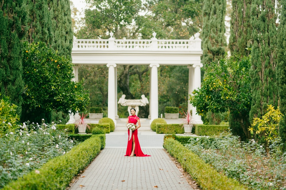 woman in red dress walking on pathway during daytime